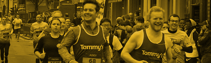 Two men running in Tommy's running vests