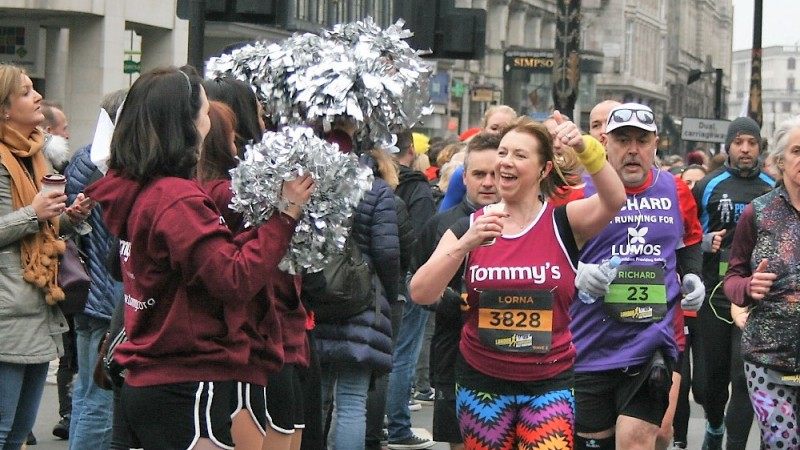 Woman running while being cheered