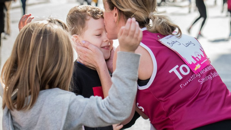 A Tommy's runner stopping to kiss her son